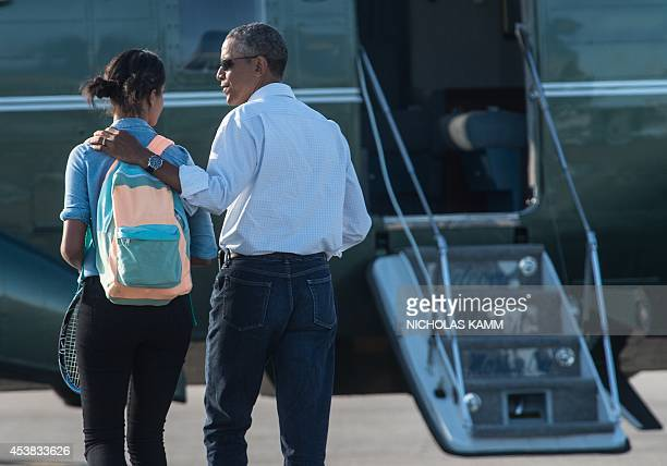 US President Barack Obama and daughter Malia walk towards Marine One at Cape Cod Coast Guard Air Station in Massachusetts on August 19 2014 as he...