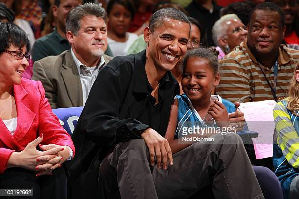 President Barack Obama and daughter Sasha Obama share a moment during the game between the Washington Mystics and the Tulsa Shock at the Verizon...