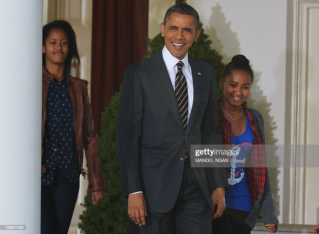 US President Barack Obama and daughters Malia and Sasha (R) arrive for the annual Thanksgiving turkey pardon November 21 , 2012 at the Rose Garden of the White House in Washington, DC. Obama pardoned Cobbler and its alternate Gobbler, both raised in Rockingham County, Virginia. The turkeys will then spend the rest of the holiday season on display at George Washington's Mount Vernon estate. AFP PHOTO/Mandel NGAN