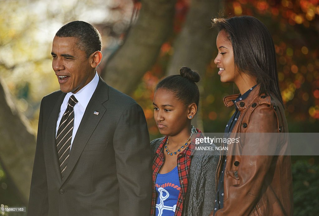 US President Barack Obama and daughters Sasha (C) and Malia look at the turkey named Cobbler during the annual Thanksgiving turkey pardon on November 21 , 2012 at the White House in Washington, DC. Obama pardoned Cobbler and its alternate Gobbler, both raised in Rockingham County, Virginia. The turkeys will then spend the rest of the holiday season on display at George Washington's Mount Vernon estate. AFP PHOTO/Mandel NGAN