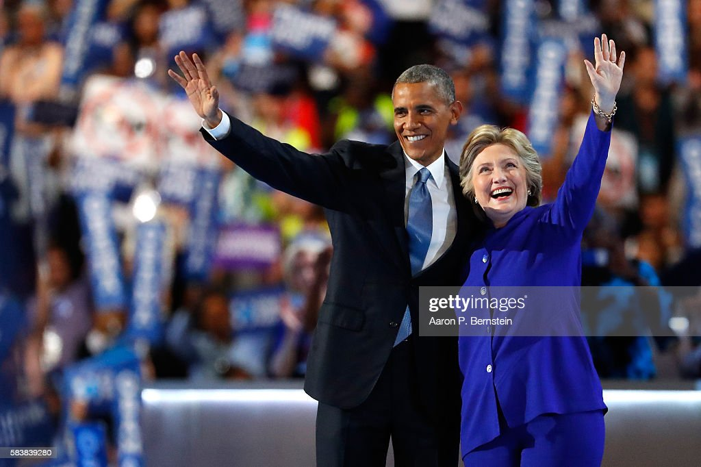 US President Barack Obama and Democratic Presidential nominee Hillary Clinton wave to the crowd on the third day of the Democratic National Convention at the Wells Fargo Center, July 27, 2016 in Philadelphia, Pennsylvania. Democratic presidential candidate Hillary Clinton received the number of votes needed to secure the party's nomination. An estimated 50,000 people are expected in Philadelphia, including hundreds of protesters and members of the media. The four-day Democratic National Convention kicked off July 25.