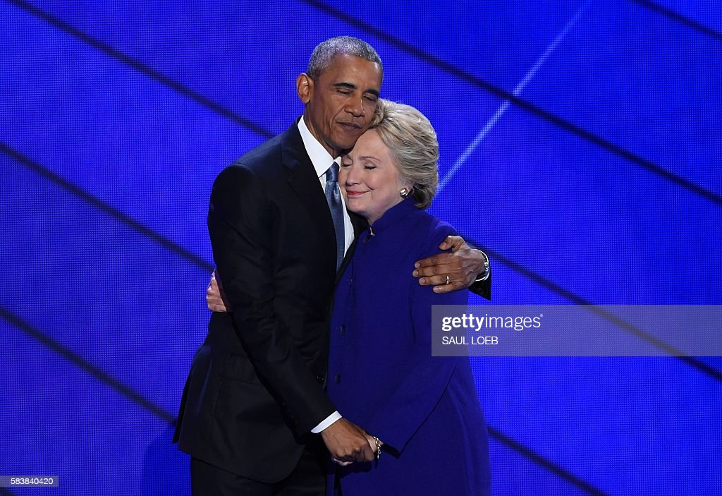 President Barack Obama and Democratic presidential nominee Hillary Clinton embrace on stage during Day 3 of the Democratic National Convention at the Wells Fargo Center, July 27, 2016 in Philadelphia, Pennsylvania. / AFP / SAUL