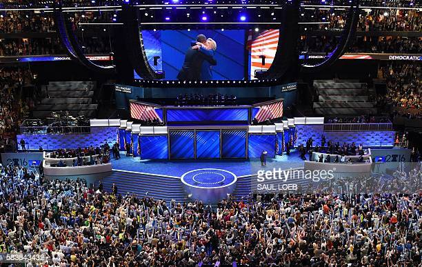 US President Barack Obama and Democratic presidential nominee Hillary Clinton embrace on stage during Day 3 of the Democratic National Convention at...