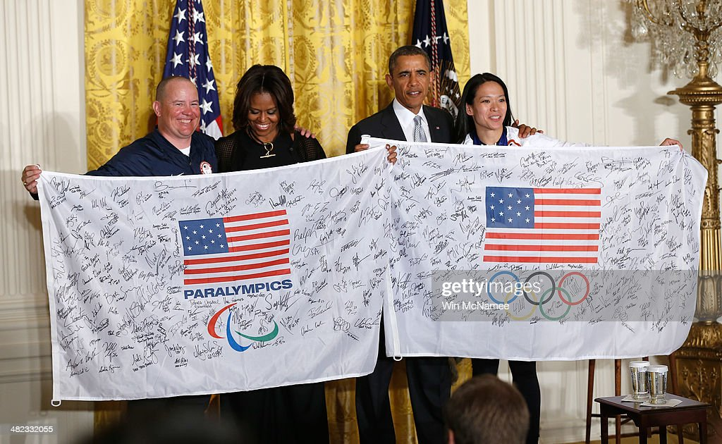 U.S. President Barack Obama and first lady Michelle Obama accept autographed U.S. Olympic flags from Jon Lujan (L) of Littleton, Colorado, Paralympics Alpine Skiing, former US Marine Corps Sergeant and 2014 Winter Paralympic Games Opening Ceremony Team USA Flag Bearer; and Julie Chu of Fairfield, Connecticut, WomenÕs Ice Hockey and 2014 Winter Olympic Games Closing Ceremony Team USA Flag Bearer, during an event in the East Room of the White House April 3, 2014 in Washington, DC. Obama congratulated the Olympians and Paralympians on their performance and thanked them for representing the U.S. during the 2014 Olympic Winter Games in Sochi, Russia.