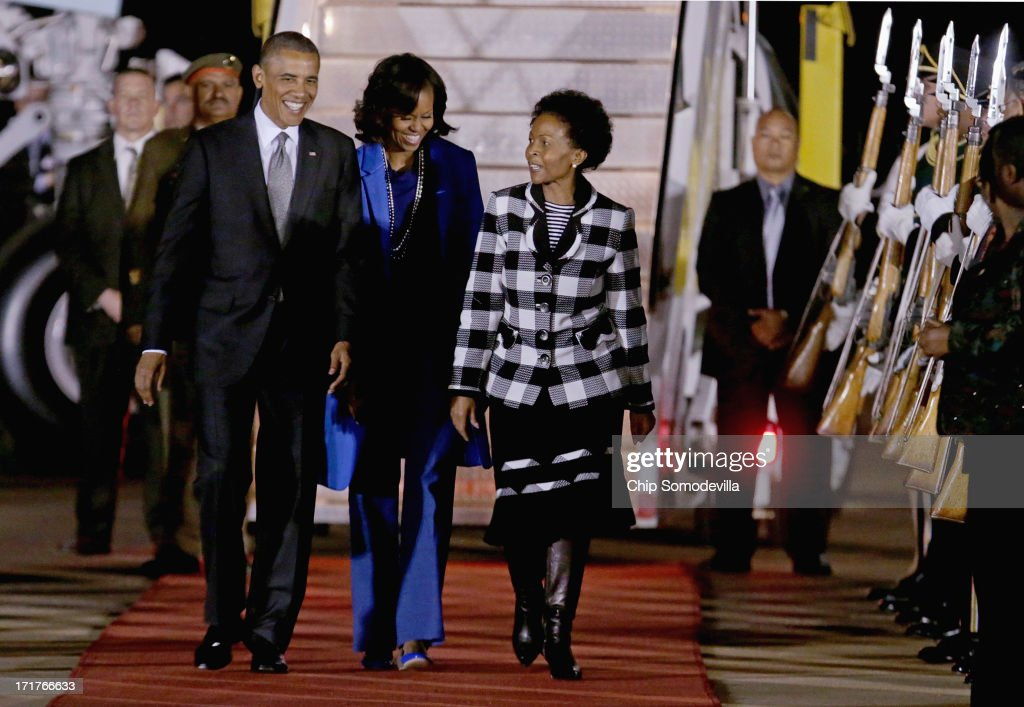 U.S. President <a gi-track='captionPersonalityLinkClicked' href=/galleries/search?phrase=Barack+Obama&family=editorial&specificpeople=203260 ng-click='$event.stopPropagation()'>Barack Obama</a> (L) and first lady <a gi-track='captionPersonalityLinkClicked' href=/galleries/search?phrase=Michelle+Obama&family=editorial&specificpeople=2528864 ng-click='$event.stopPropagation()'>Michelle Obama</a> (C) are greeted by Minister of International Relations and Cooperation Maite Mkoana-Mashabne after arriving at Waterkloof Air Force Base June 28, 2013 in Pretoria, South Africa. This is Obama's first official visit to South Africa, where is schedule to hold bilaterial meetings with President Jacob Zuma, host a town hall meeting with students in Soweto Township and visit Robben Island, where former President Nelson Mandela spent some of his 27 years in prison for fighting against apartheid.