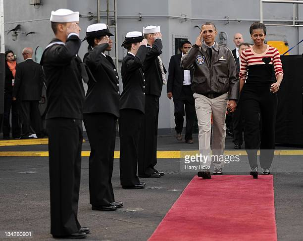 S President Barack Obama and first lady Michelle Obama are saluted as they make their way to their seats before the game between the North Carolina...