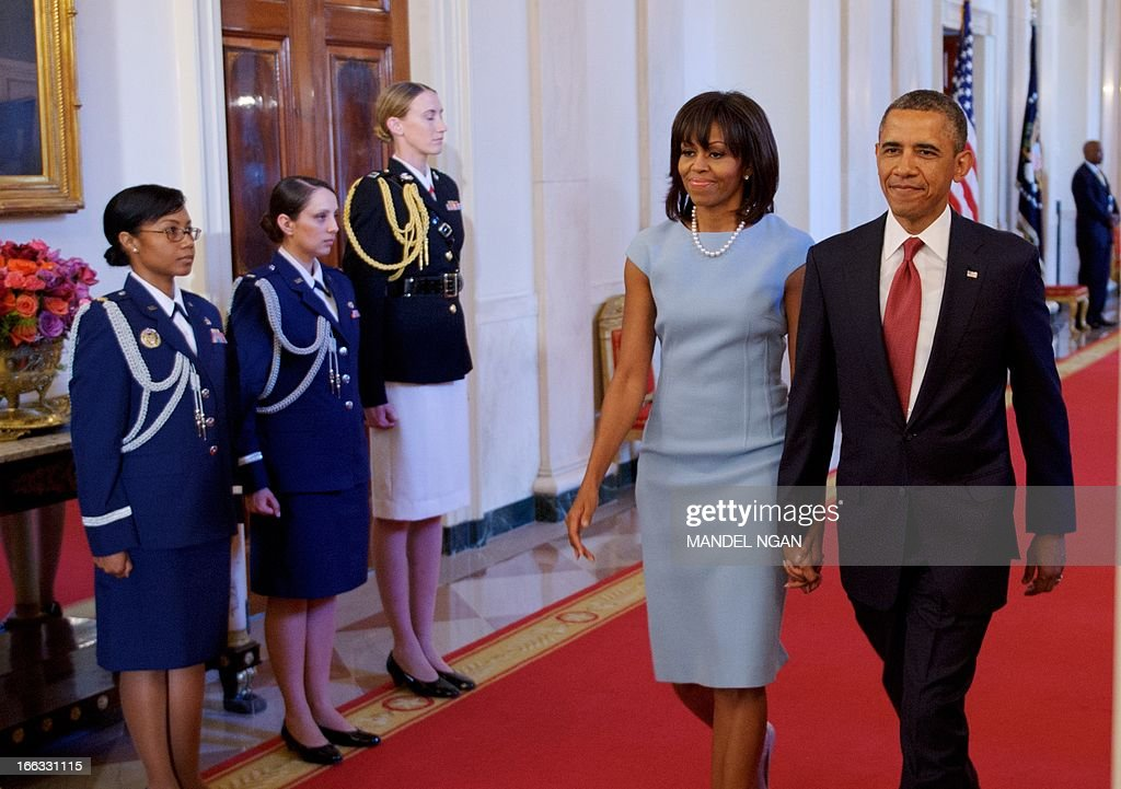 US President <a gi-track='captionPersonalityLinkClicked' href=/galleries/search?phrase=Barack+Obama&family=editorial&specificpeople=203260 ng-click='$event.stopPropagation()'>Barack Obama</a> and First Lady Michelle Obama arrive for a medal of honor presentation ceremony for US Army Chaplain (Captain) Emil J. Kapaun on April 11, 2013 in the East Room of the White House in Washington, DC. Kapuan was awarded the medal posthumously for his service with the 3d Battalion, 8th Cavalry Regiment, 1st Cavalry Division during combat operations against an armed enemy at Unsan, Korea. AFP PHOTO/Mandel NGAN
