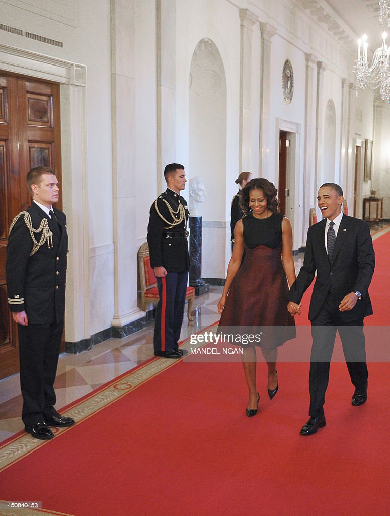 US President Barack Obama and First Lady Michelle Obama arrive for the Presidential Medal of Freedom presentation ceremony in the East Room of the White House on November 20, 2013 in Washington, DC. The Medal of Freedom is the country's highest civilian honor. AFP PHOTO/Mandel NGAN