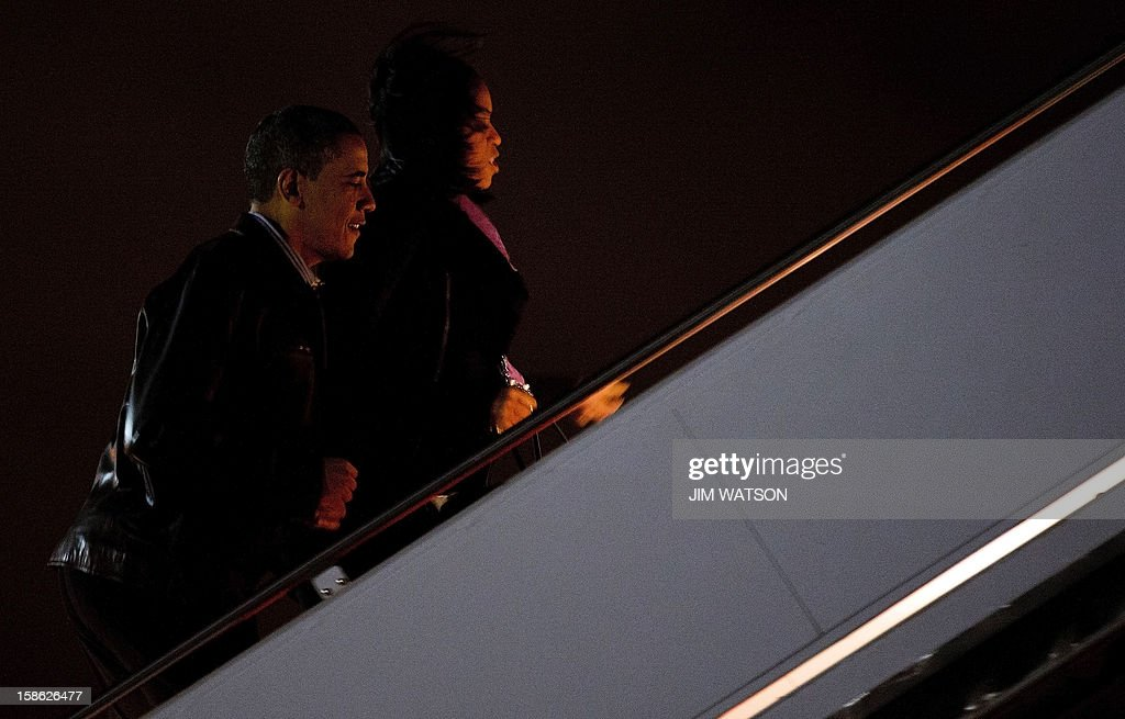 US President Barack Obama (L) and First Lady Michelle Obama board Air Force One at Andrews Air Force Base, MD, December 21, 2012, en route to Honolulu, Hawaii. US President Barack Obama told lawmakers to go home and drink some Christmas egg nog before coming back to Washington to pass a scaled-down tax package to avert a year-end fiscal crisis. Obama said he still wanted a comprehensive and large deficit-cutting bill to put the US economy on the path to long-term prosperity, but that effort stalled when talks broke down between the White House and House Republicans this week. AFP Photo/Jim WATSON
