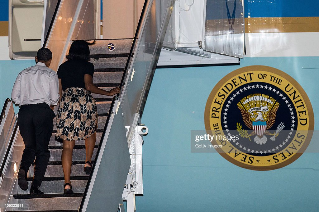US President Barack Obama and First Lady Michelle Obama board Air Force One at Joint Base Pearl Harbor-Hickam on January 5, 2013 in Honolulu, Hawaii. The president had to cut short his vacation to work in Washington on efforts to avert the recent fiscal cliff crisis and then returned to Hawaii to be with his family.