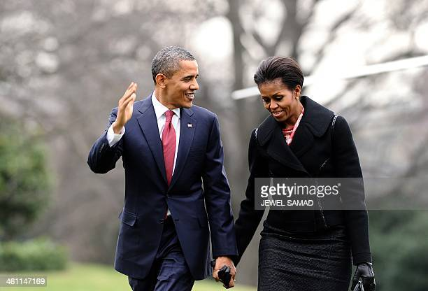 US President Barack Obama and First Lady Michelle Obama chat as they walk to the White House in Washington DC on December 14 2011 upon returing from...