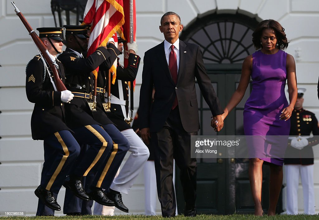 U.S. President <a gi-track='captionPersonalityLinkClicked' href=/galleries/search?phrase=Barack+Obama&family=editorial&specificpeople=203260 ng-click='$event.stopPropagation()'>Barack Obama</a> and first lady <a gi-track='captionPersonalityLinkClicked' href=/galleries/search?phrase=Michelle+Obama&family=editorial&specificpeople=2528864 ng-click='$event.stopPropagation()'>Michelle Obama</a> come out from the White House to observe a moment of silence to mark the 12th anniversary of the 9/11 attacks September 11, 2013 on the South Lawn of the White House in Washington, DC. The nation is commemorating the anniversary of the 2001 attacks which resulted in the deaths of nearly 3,000 people after two hijacked planes crashed into the World Trade Center, one into the Pentagon in Arlington, Virginia and one crash landed in Shanksville, Pennsylvania.