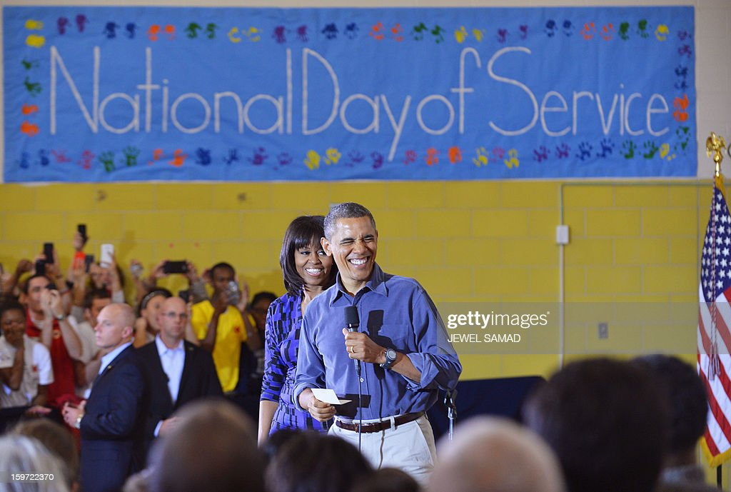 US President Barack Obama and First Lady Michelle Obama greet a crowd of people at Burrville Elementary School after participating in National Day of Service on January 19, 2013 in Washington DC, as part of the 57th Presidential Inauguration. Americans across the country participate in service projects in their communities to celebrate the legacy of civil rights leader Dr. Martin Luther King, Jr. The holiday honoring King will be observed on January 21, the day of the second inauguration of US President Barack Obama and Vice President Biden. AFP PHOTO/Jewel Samad