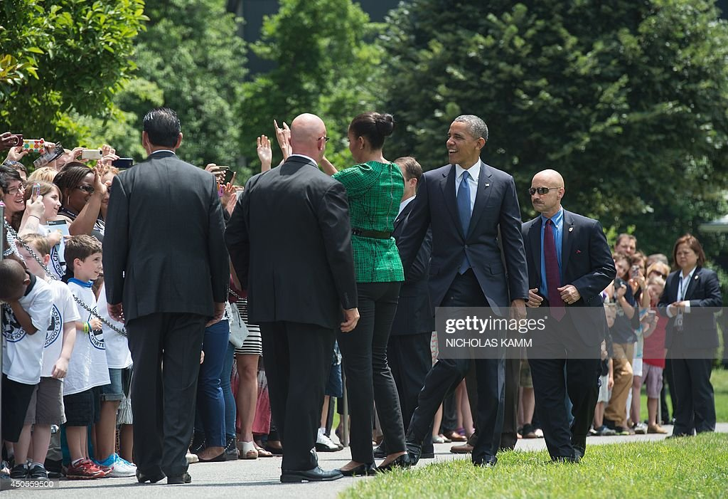 US President <a gi-track='captionPersonalityLinkClicked' href=/galleries/search?phrase=Barack+Obama&family=editorial&specificpeople=203260 ng-click='$event.stopPropagation()'>Barack Obama</a> and First Lady Michelle Obama greet wellwishers before departing the White House in Washington on June 13, 2014. The Obamas travel to the Cannon Ball, North Dakota, area to visit the Standing Rock Sioux Tribal Nation. AFP PHOTO/Nicholas KAMM