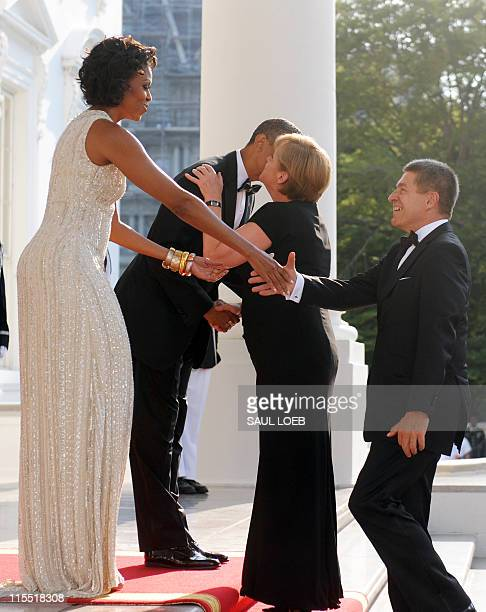 US President Barack Obama and First Lady Michelle Obama greet German Chancellor Angela Merkel and her husband Joachim Sauer at the North Portico of...