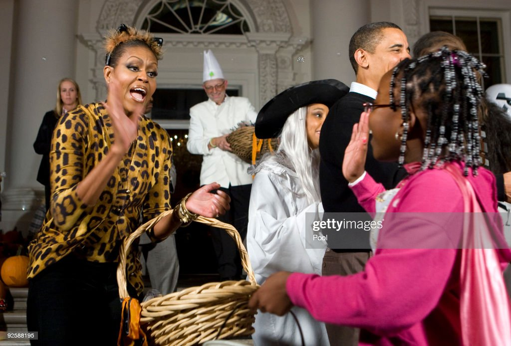 President Barack Obama and first lady Michelle Obama greet parents, trick-or-treaters and local school children at the north portico of the White House during a Halloween celebration on October 31, 2009 in Washington, DC. The Obamas are celebrating their first Halloween in the White House by inviting students and military families over for the holiday.