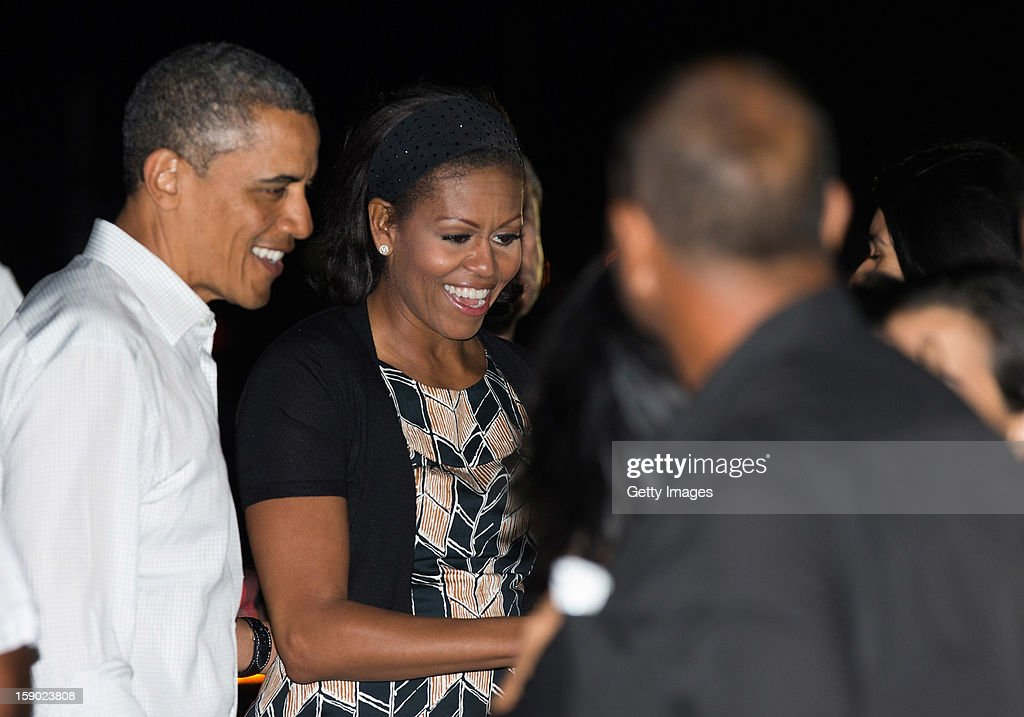 US President Barack Obama and First Lady Michelle Obama greet well wishers before boarding Air Force One at Joint Base Pearl Harbor-Hickam on January 5, 2013 in Honolulu, Hawaii. The president had to cut short his vacation to work in Washington on efforts to avert the recent fiscal cliff crisis and then returned to Hawaii to be with his family.
