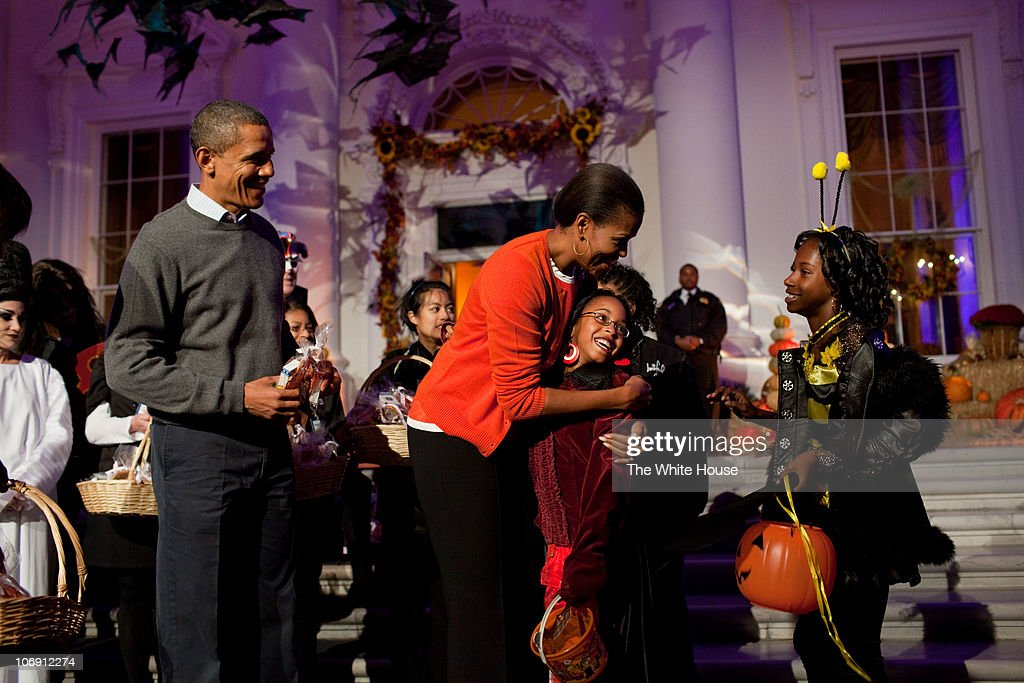 President Barack Obama and first lady Michelle Obama hand out Halloween treats to children on the North Portico of the White House on Octtober 31, 2010 in Washington DC.