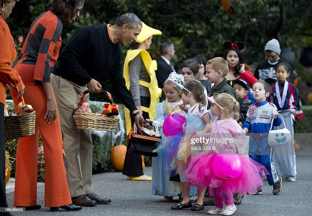 US President Barack Obama and First Lady Michelle Obama hand out treats to local children and children of military families as they trick-or-treat for Halloween on the South Lawn of the White House in Washington, DC, October 31, 2013. AFP PHOTO / Saul LOEB