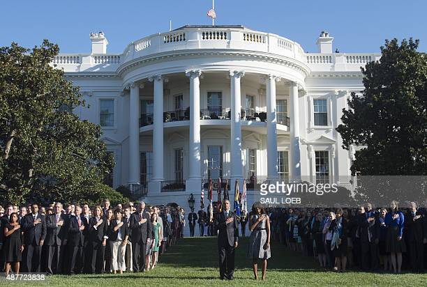 US President Barack Obama and First Lady Michelle Obama hold a moment of silence on the South Lawn of the White House in Washington DC September 11...