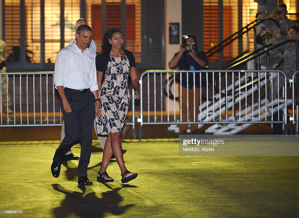 US President Barack Obama and First Lady Michelle Obama (2nd L) make their way to board Air Force One on January 5, 2013 upon departure from Hickam Air Force Base in Honolulu, Hawaii. Obama was to return to Washington, DC after vacationing in Hawaii. AFP PHOTO / Mandel NGAN