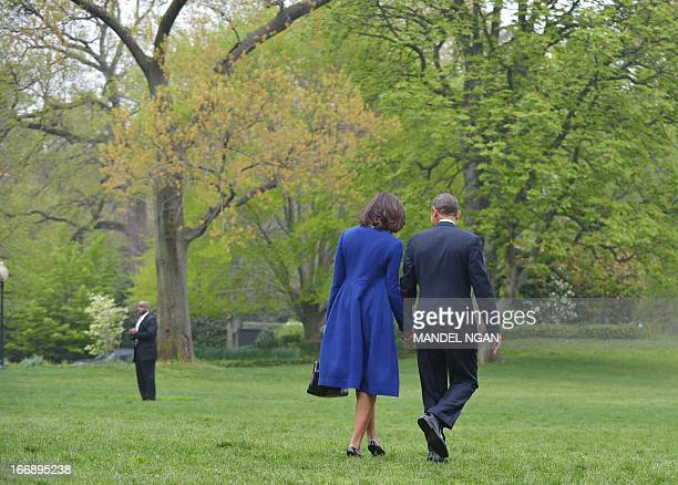 US President Barack Obama and First Lady Michelle Obama make their way across the South Lawn to board Marine One on April 18 2013 at the White House...