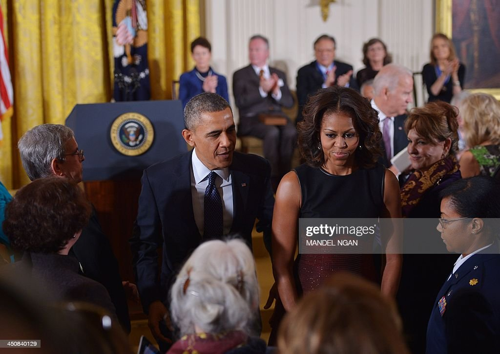 US President Barack Obama and First Lady Michelle Obama make their way from the East Room following the Presidential Medal of Freedom presentation ceremony on November 20, 2013 in Washington, DC. The Medal of Freedom is the country's highest civilian honor. AFP PHOTO/Mandel NGAN