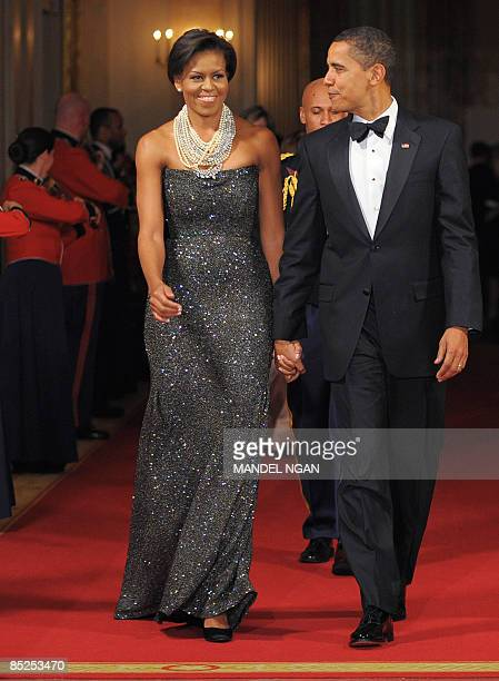 US President Barack Obama and First Lady Michelle Obama make their way into the East Room for after dinner entertainment with US governors February...