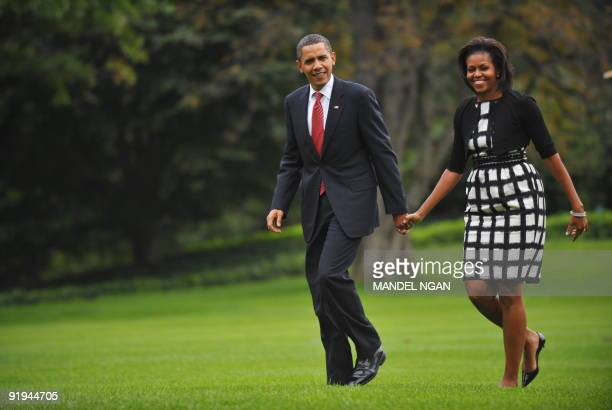 US President Barack Obama and First Lady Michelle Obama make their way from Marine One October 2 2009 upon return to the White House in Washington DC...