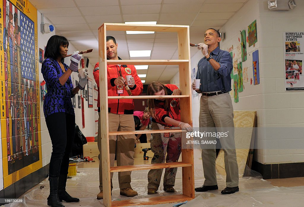 US President Barack Obama (R) and First Lady Michelle Obama (L) paint a bookshelf at Burrville Elementary School during Day of Service on January 19, 2013 in Washington DC, as part of the 57th Presidential Inauguration. Americans across the country participate in service projects in their communities to celebrate the legacy of civil rights leader Dr. Martin Luther King, Jr. The holiday honoring King will be observed on January 21, the day of the second inauguration of US President Barack Obama and Vice President Biden. AFP PHOTO/Jewel Samad