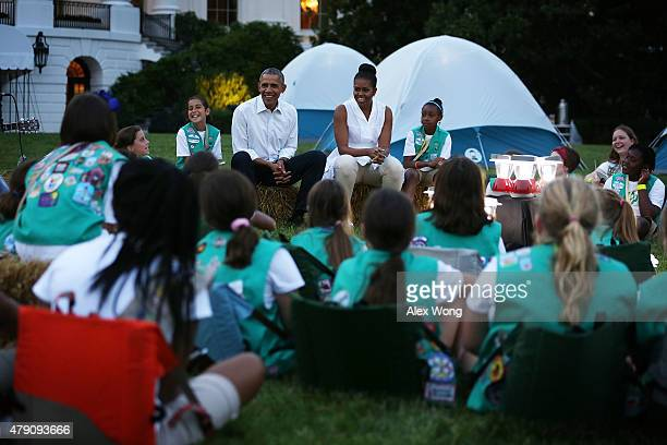 S President Barack Obama and first lady Michelle Obama participate in a campfire songs session with fourthgrade Girl Scouts during the firstever...
