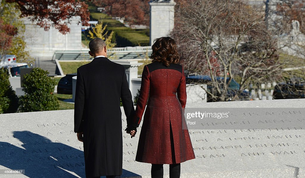 U.S. President Barack Obama and first lady Michelle Obama pause at the memorial for President John F. Kennedy at Arlington National Cemetery November 20, 2013 in Arlington, Virginia. The 50th anniversary of the assassination of John F. Kennedy will be marked on November 22.