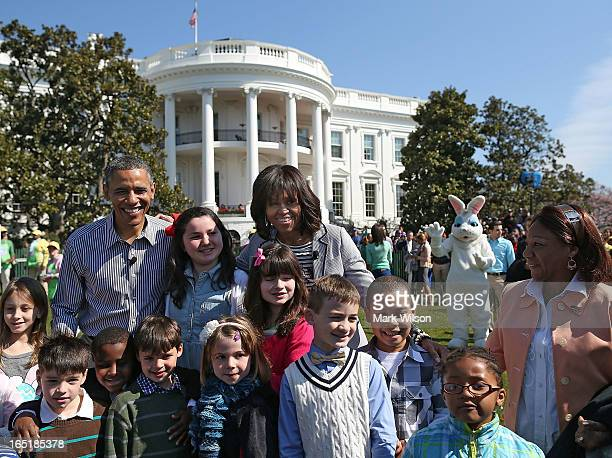 S President Barack Obama and first lady Michelle Obama pose for photos with children during the annual Easter Egg Roll on the White House tennis...