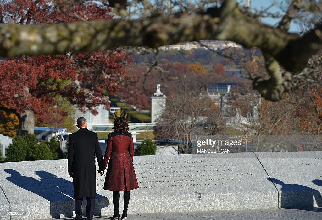 US President Barack Obama and First Lady Michelle Obama read an inscription after taking part in a wreath-laying ceremony in honor of the late US President John F. Kennedy at Arlington National Cemetery on November 20, 2013 in Arlington, Virginia. AFP PHOTO/Mandel NGAN
