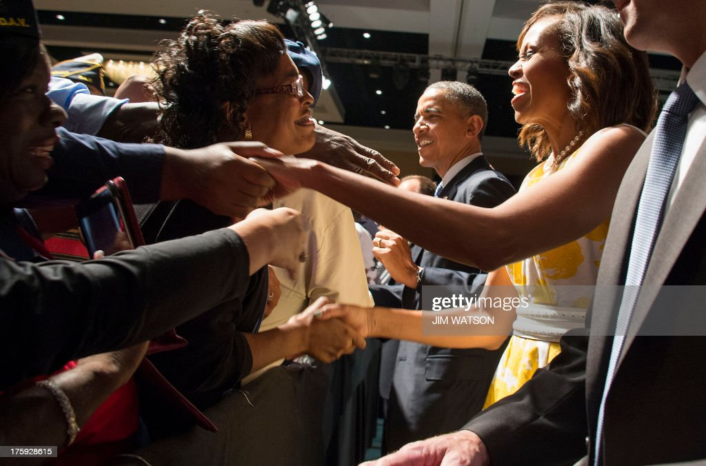 US President <a gi-track='captionPersonalityLinkClicked' href=/galleries/search?phrase=Barack+Obama&family=editorial&specificpeople=203260 ng-click='$event.stopPropagation()'>Barack Obama</a> (C) and First Lady Michelle Obama (R) shake hands after addressing injured veterans at the Disabled American Veterans National Convention in Orlando, Florida, August 10, 2013. Obama cited progress in reducing the backlog of disability claims from disabled veterans. AFP PHOTO/Jim WATSON