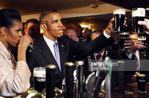 US President Barack Obama and First Lady Michelle Obama sip Guinness at a pub as they visit Moneygall village in rural County Offaly Ireland where...
