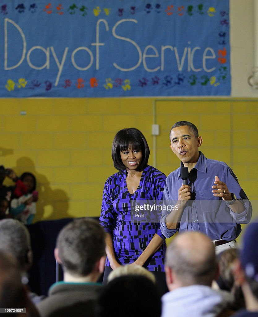 President Barack Obama (R) and first lady Michelle Obama speak to volunteers at Burrville Elementary School January 19, 2013 in Washington, DC. The event was part of the National Day of Service, the first official event of the 57th presidential inauguration weekend.