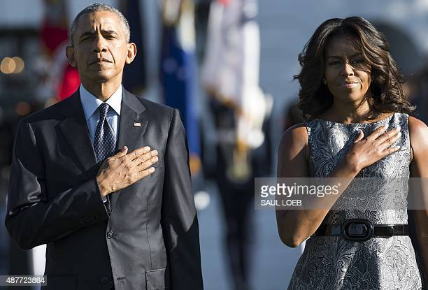 US President Barack Obama and First Lady Michelle Obama stand on the South Lawn of the White House in Washington DC September 11 to mark the 14th...