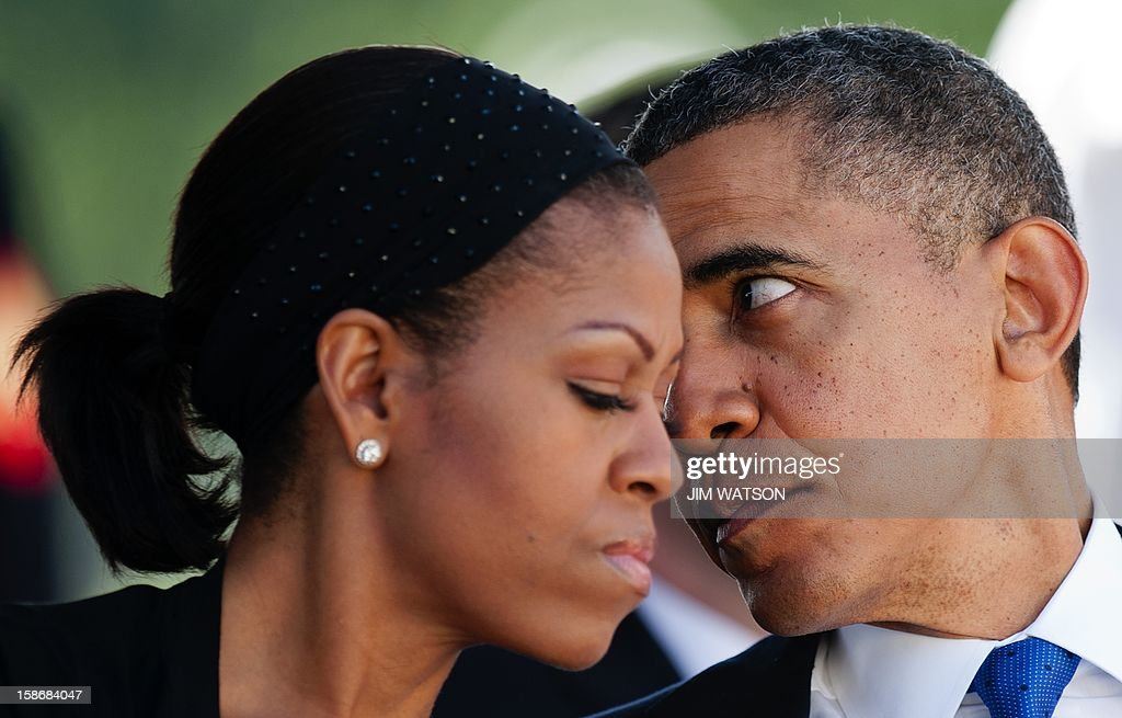 US President Barack Obama (R) and First Lady Michelle Obama talk as they attends the memorial service for the late Senator Daniel Inouye at the National Memorial Cremetary of the Pacific in Honolulu, Hawaii, December 23, 2012. AFP Photo/Jim WATSON