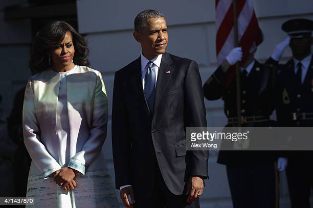 US President Barack Obama and first lady Michelle Obama wait for the arrival of Japanese Prime Minister Shinzo Abe and his wife Akie Abe during an...
