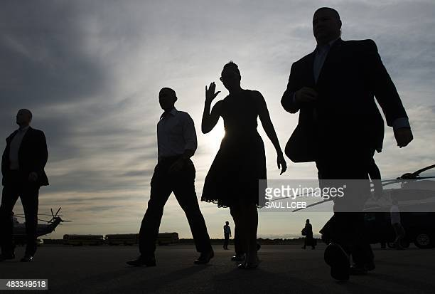 US President Barack Obama and First Lady Michelle Obama walk from Marine One upon arrival on Martha's Vineyard in Massachusetts August 7 2015 The...