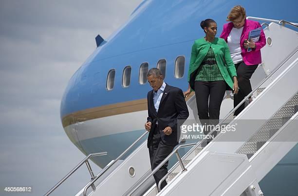US President Barack Obama and First Lady Michelle Obama walk off Air Force One with US Democratic Senator from North Dakota Heidi Heitkamp in Bismark...