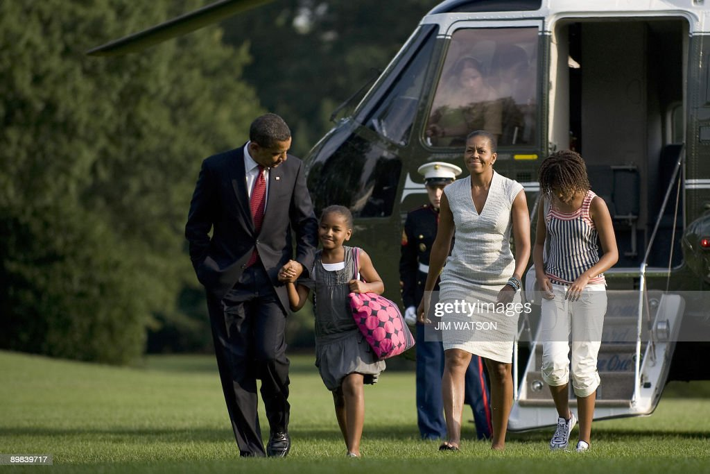 US President <a gi-track='captionPersonalityLinkClicked' href=/galleries/search?phrase=Barack+Obama&family=editorial&specificpeople=203260 ng-click='$event.stopPropagation()'>Barack Obama</a> (L) and First Lady <a gi-track='captionPersonalityLinkClicked' href=/galleries/search?phrase=Michelle+Obama&family=editorial&specificpeople=2528864 ng-click='$event.stopPropagation()'>Michelle Obama</a> (2nd R) walk off MArine One with their daughters Malia (R) and Sasha as they return the the White House in Washington on August 17, 2009. AFP PHOTO/Jim WATSON