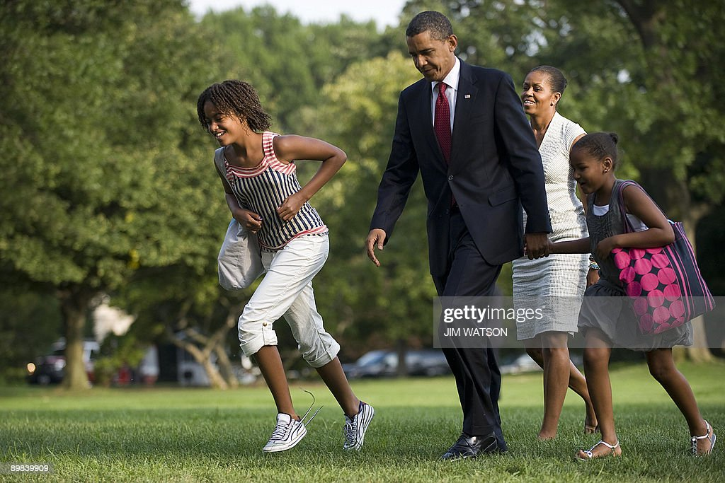 US President <a gi-track='captionPersonalityLinkClicked' href=/galleries/search?phrase=Barack+Obama&family=editorial&specificpeople=203260 ng-click='$event.stopPropagation()'>Barack Obama</a> (C) and First Lady <a gi-track='captionPersonalityLinkClicked' href=/galleries/search?phrase=Michelle+Obama&family=editorial&specificpeople=2528864 ng-click='$event.stopPropagation()'>Michelle Obama</a> (2nd R) walk off Marine One with their daughters Malia (L) and Sasha (R) as they return the the White House in Washington on August 17, 2009. AFP PHOTO/Jim WATSON