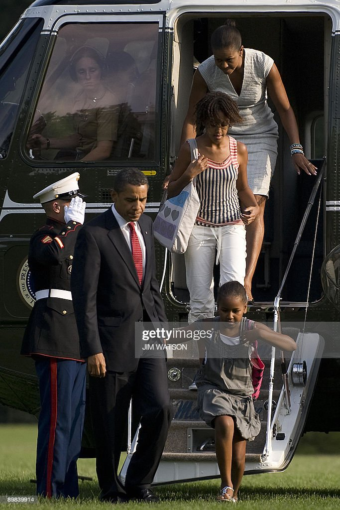 US President <a gi-track='captionPersonalityLinkClicked' href=/galleries/search?phrase=Barack+Obama&family=editorial&specificpeople=203260 ng-click='$event.stopPropagation()'>Barack Obama</a> (L) and First Lady <a gi-track='captionPersonalityLinkClicked' href=/galleries/search?phrase=Michelle+Obama&family=editorial&specificpeople=2528864 ng-click='$event.stopPropagation()'>Michelle Obama</a> (top) walk off Marine One with daughters Malia (C) and Sasha (R) as they return to the White House in Washington on August 17, 2009. AFP PHOTO/Jim WATSON