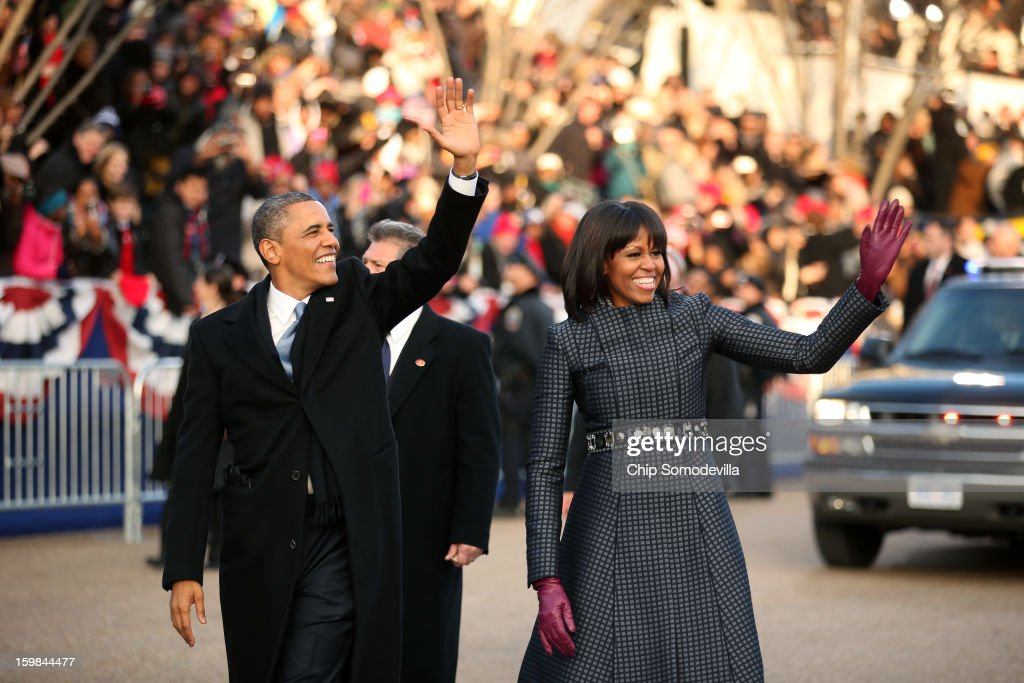 U.S. President Barack Obama (L) and first lady Michelle Obama walk the route as the presidential inaugural parade winds through the nation's capital January 21, 2013 in Washington, DC. Barack Obama was re-elected for a second term as President of the United States.