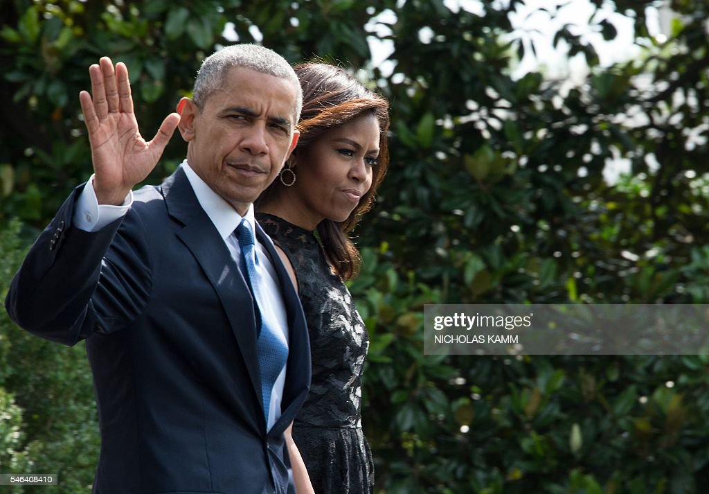 US President Barack Obama and First Lady Michelle Obama walk to board Marine One on July 12 2016 at the White House in Washington DC before departing...