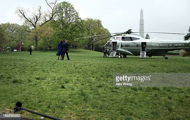 S President Barack Obama and first lady Michelle Obama walk toward the Marine One prior to their departure for Boston April 18 2013 in Washington DC...