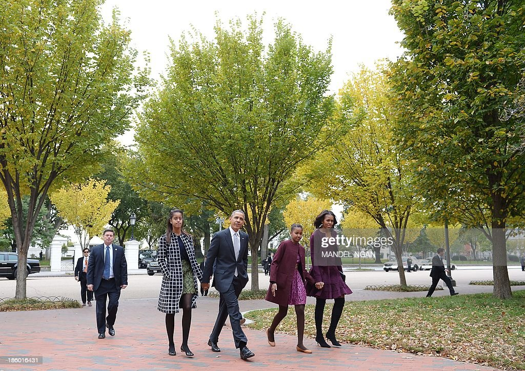 US President Barack Obama and First Lady Michelle Obama walk with daughters Malia (L) and Sasha (2nd R) across Lafayette Park to Saint John's Episcopal Chuch for Sunday services on October 27, 2013 in Washington, DC. AFP PHOTO/Mandel NGAN