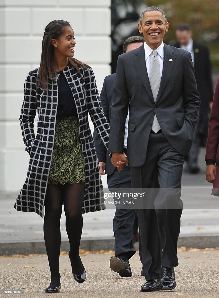 US President Barack Obama and First Lady Michelle Obama walk with daughter Malia (L) across Lafayette Park to Saint John's Episcopal Chuch for Sunday services on October 27, 2013 in Washington, DC. AFP PHOTO/Mandel NGAN